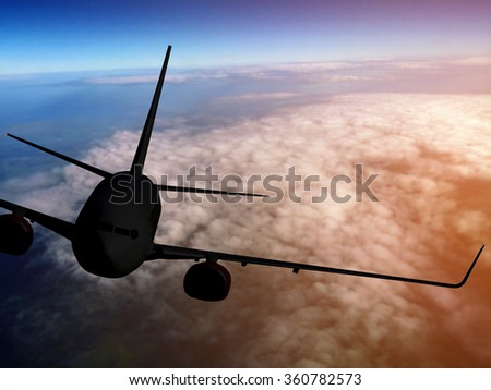 Airplane flying above clouds the on sunset - stock photo