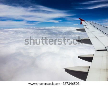 Airplane flying above cloudy, space left of frame. - stock photo