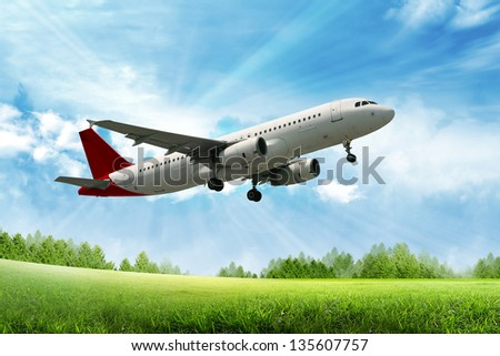 airplane flying above green field - stock photo