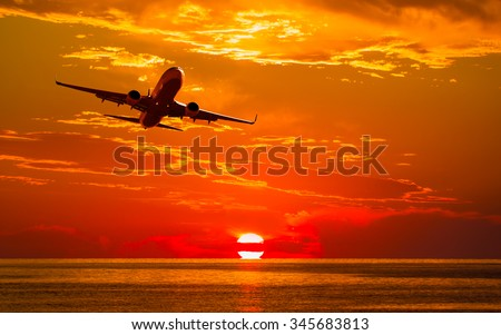 Airplane flying above tropical sea at sunset - stock photo