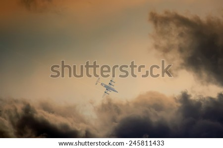 airplane flying close to the storm in sunset time  - stock photo