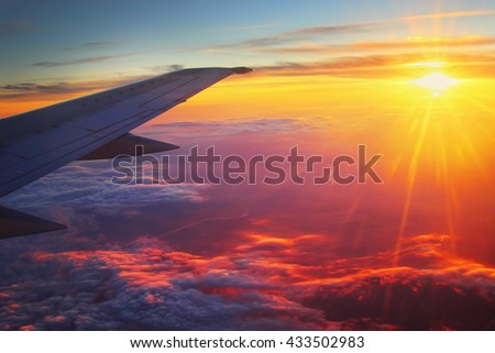 Airplane flying high above the clouds at sunset. - stock photo