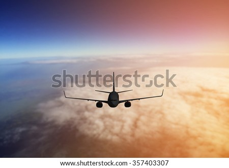 Airplane flying on sky at sunset - stock photo