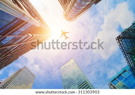 Airplane flying over business skyscrapers, high-rise buildings. Transport, transportation, travel. Sun light on blue sky. - stock photo