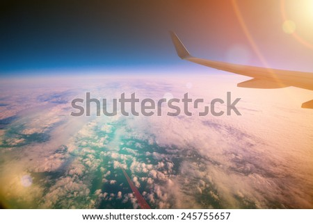 Airplane flying over clouds at sunrise   - stock photo