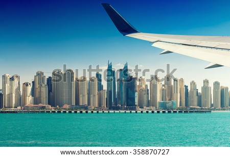 Airplane flying over Dubai skyscrapers, UAE. - stock photo