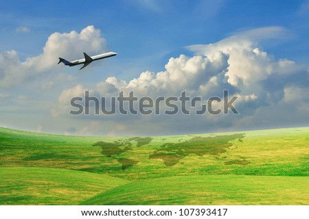 Airplane flying over green field with blue sky - stock photo