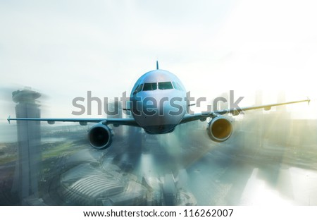Airplane flying over high buildings - stock photo