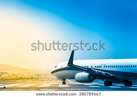 Airplane goes at taxiway to the position for takeoff at an airport runway at bright colorful sunrise morning/Plane Rolling to Take Off - stock photo