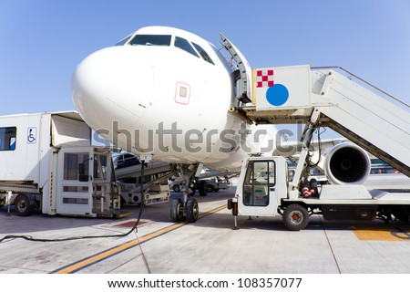 Airplane in airport serviced by the ground crew - stock photo