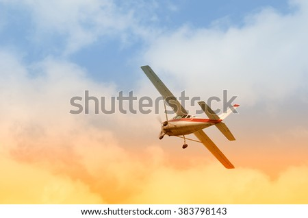 Airplane in flight with cloudy sky at sunset in summer - stock photo
