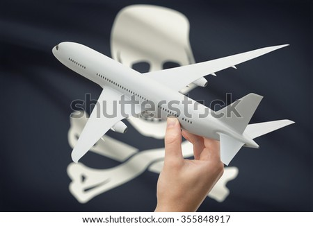 Airplane in hand with local US state flag on background - Jolly Roger - symbol of piracy - stock photo