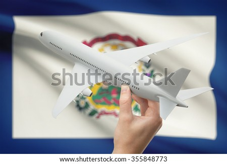 Airplane in hand with local US state flag on background - West Virginia - stock photo