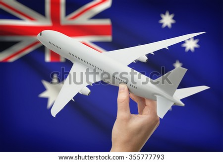 Airplane in hand with national flag on background - Australia - stock photo