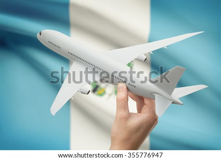 Airplane in hand with national flag on background - Guatemala - stock photo