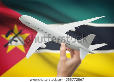 Airplane in hand with national flag on background - Mozambique - stock photo
