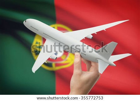 Airplane in hand with national flag on background - Portugal - stock photo