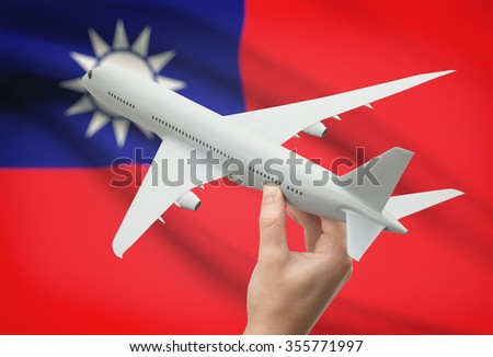 Airplane in hand with national flag on background - Republic of China - Taiwan - stock photo