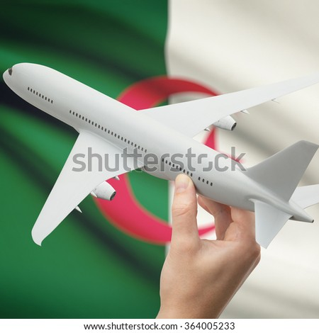Airplane in hand with national flag on background series - Algeria - stock photo