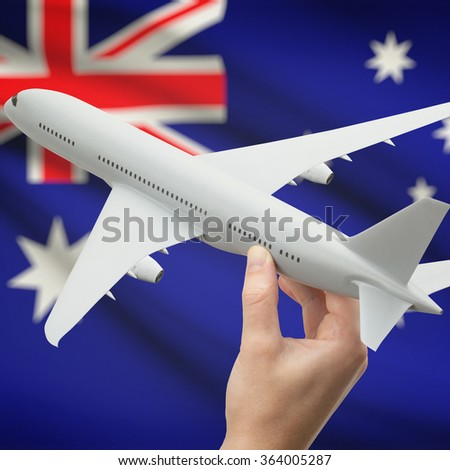 Airplane in hand with national flag on background series - Australia - stock photo