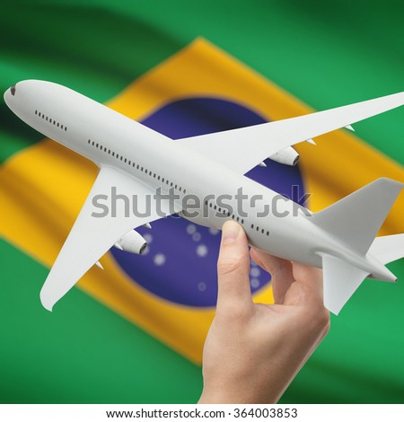 Airplane in hand with national flag on background series - Brazil - stock photo