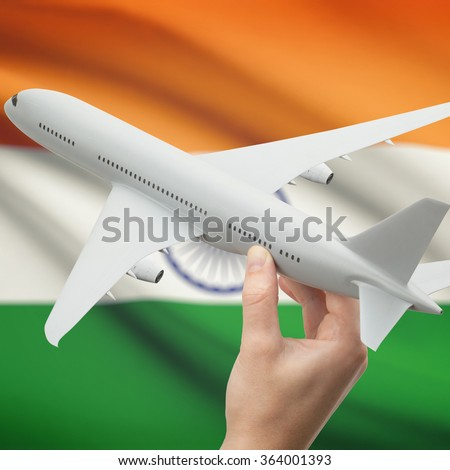 Airplane in hand with national flag on background series - India - stock photo