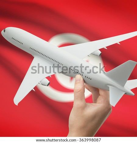 Airplane in hand with national flag on background series - Tunisia - stock photo