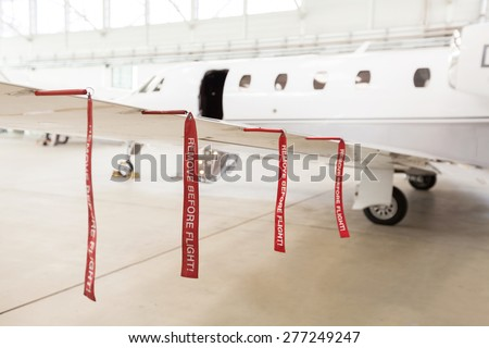 Airplane in Hangar with remove before flight Labels in red - stock photo