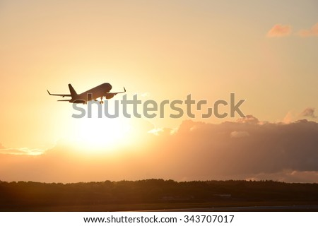 Airplane in the air and sunset in background - stock photo