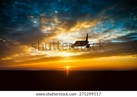 Airplane in the sky at sunset clouds - stock photo