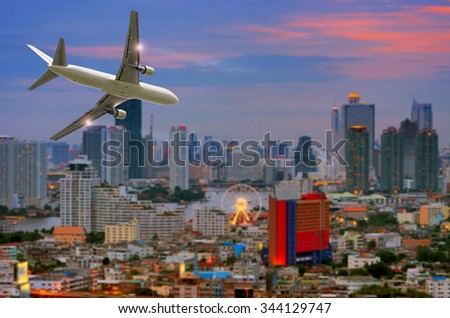 Airplane in the sky at sunset Flying over the city and river. - stock photo