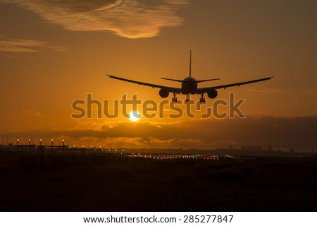 Airplane is landing during a nice cloudy sunrise. - stock photo