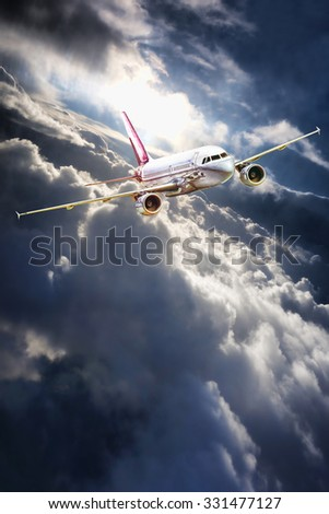 Airplane is leaving from thunderstorms with sunbeams - stock photo
