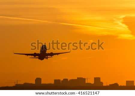 Airplane is taking off from the airport at dusk. - stock photo