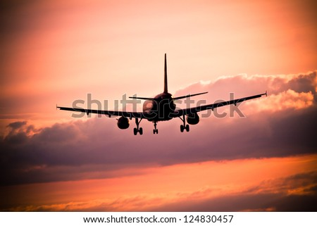 Airplane landing at sunset - stock photo