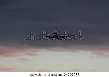 airplane landing at sunset with dark clouds background - stock photo