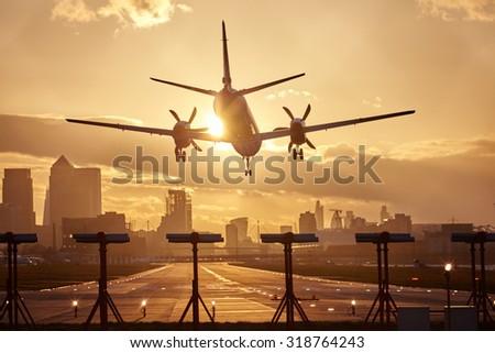 Airplane landing in sunset. - stock photo