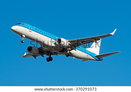 Airplane landing on a bright day in sunlight - stock photo