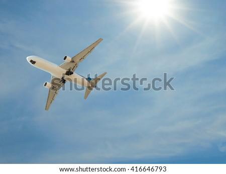 Airplane landing on sky blue sunny - stock photo