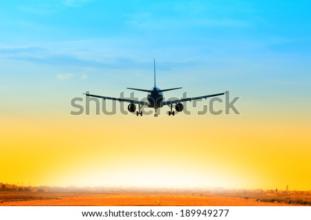 airplane landing on the runway at sunset - stock photo
