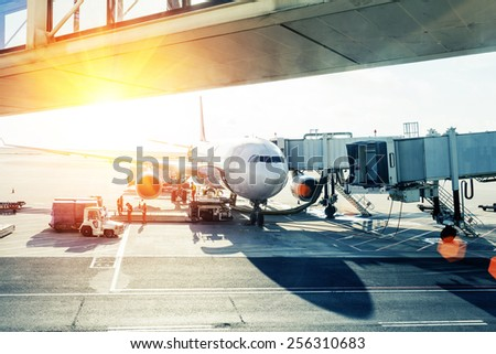 airplane loading in airport at sunset - stock photo