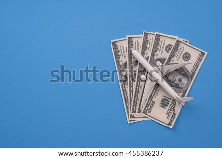 airplane model and banknote money on blue background, Budget travel concept. - stock photo