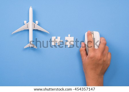 Airplane model and computer mouse on blue background, Online travel booking concept. - stock photo