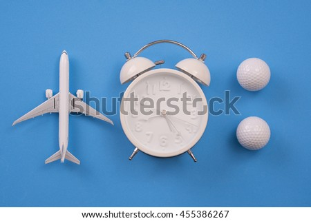 airplane model, clock and golf ball on blue background, Balance working concept. - stock photo