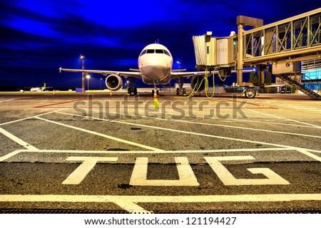 Airplane near the gate at night - stock photo