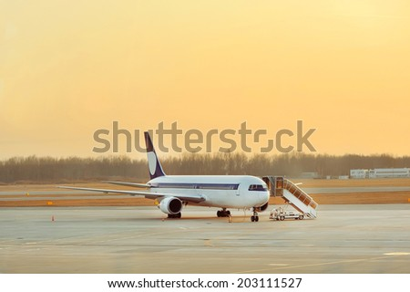Airplane near the terminal in an airport at the sunset - stock photo