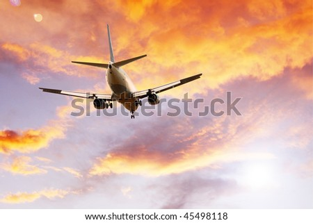 Airplane on sunset sky - stock photo