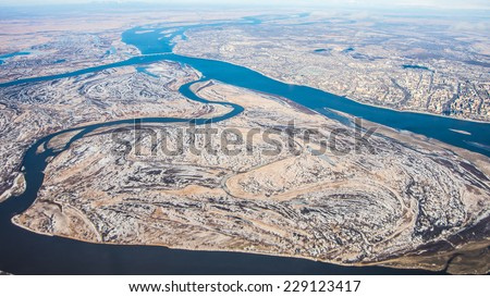 Airplane panoramic view of great Amur (Heilong Jiang) river, Khabarovsk city  and bridge which is part of Trans-Siberian railway in Khabarovsk district in Far East of Russia with first winter snow - stock photo
