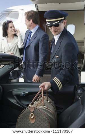 Airplane pilot putting luggage in car with business people in the background at airfield - stock photo