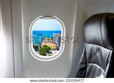 Airplane seat and window inside an aircraft with Salvador city view. - stock photo